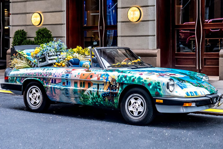 A very colorful convertible in the middle of the street with a lot of colorful things.